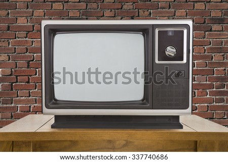 Old portable television and table with brick wall. - stock photo