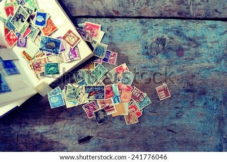 Old post stamps on a wooden background - stock photo