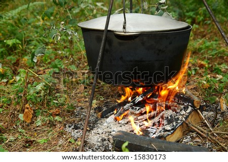 Old pot on a campfire - stock photo