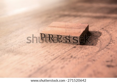 Old press stamp on old desk with incoming light. Shallow depth of field. Intentionally shot and processed in nostalgic surreal color. - stock photo