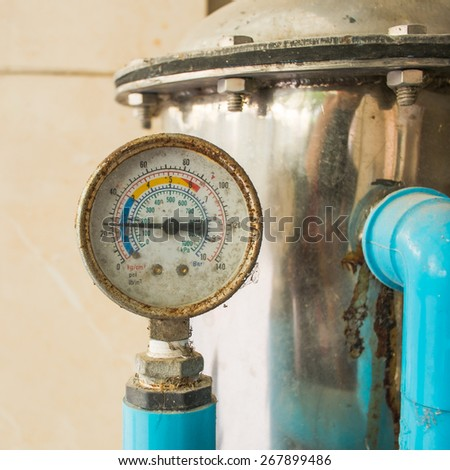 Old pressure gauge and water pump - stock photo