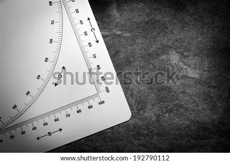 Old protractor style measuring device with algebraic symbols and graph measurements - stock photo