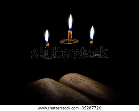 old Psalter and candles in candelabrum. Focus on candelabrum