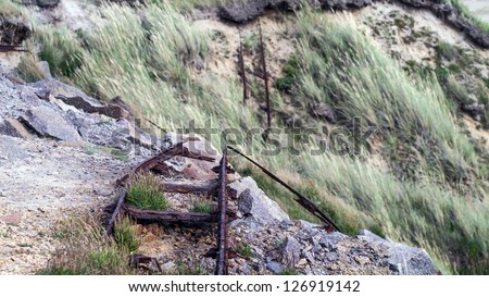 Old quarry track falling over the cliff.  Tracks were used to carry granite from a  quarry located on the northern part of Bornholm (Denmark) and were operational between 1897-1954 - stock photo