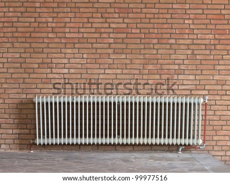 Old radiator heating device against a brick wall - stock photo