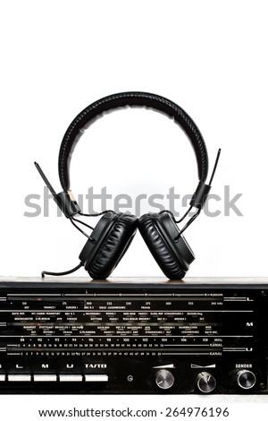 old radio with headphones on white background - stock photo