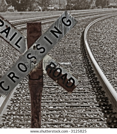 Old Railroad Crossing Sign in front of a long curve of tracks. Tinted image in dark, rich brown and black tones. - stock photo
