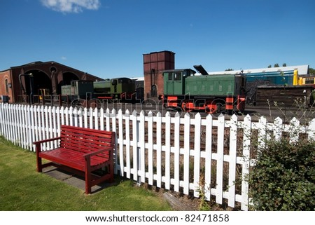 Old railway sidings with locomotives in Scotland on a bright summer day with blue sky. Bench and white fence in foreground