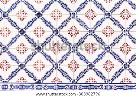 Old red and blue azulejos on the building's exterior in Lisbon, Portugal. - stock photo
