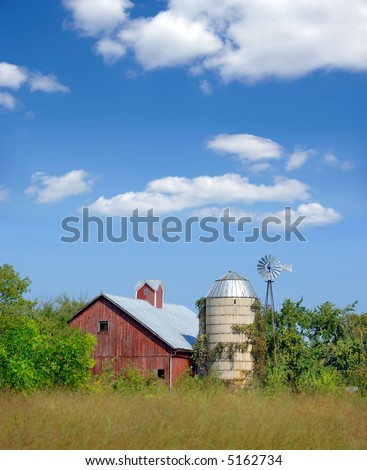 Old red barn and silo in Wisconsin. - stock photo