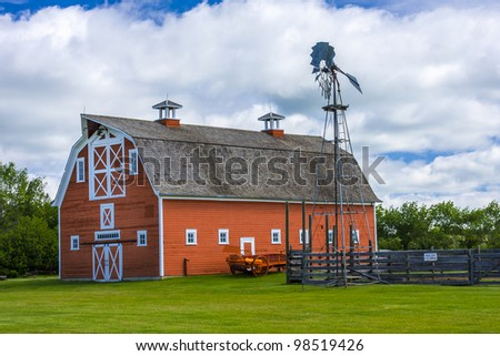 Old red barn and tall metal windmill on a farm - stock photo