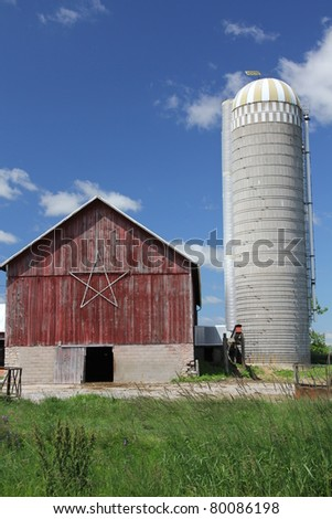 old red barn with silo - stock photo