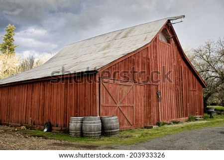 Old Red Barn, with wine barrels in front, California wine country - stock photo