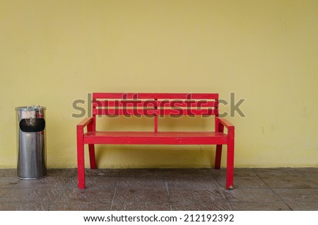 Old red bench on dirty floor and yellow wall with trash - stock photo