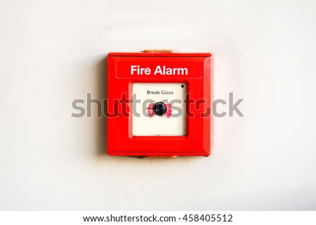Old red box fire alarm on cement wall. Fire break glass alarm switch on wall background.