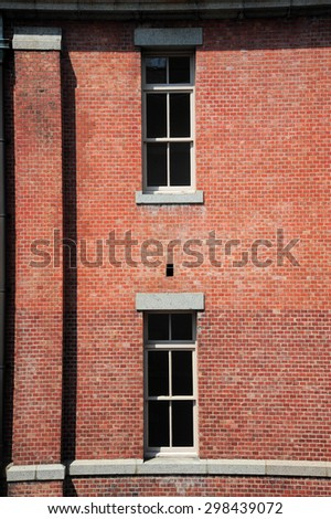 Old red brick building or factory with many windows - stock photo