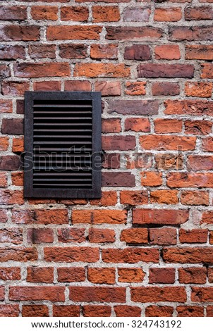 old  red brick wall and metal vent with grating - stock photo