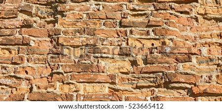 Old Red Brick Wall Wide Bumpy Texture. Rough Brickwall Horizontal Background. Grungy Stonewall Surface. Red Brown Shabby  Wreck Uneven Wall. Abstract Web Banner. Empty Clay Brick Fence Structure.