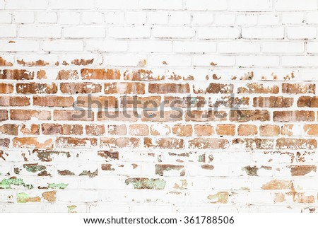 Old red brick wall with damaged white paint layer, closeup background photo texture - stock photo