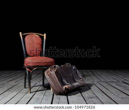 Old red chair and well-traveled vintage suitcase on wooden floor