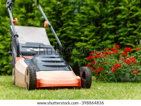 Old red electric lawn mower standing on Freshly cut green grass in summertime. View from bottom - stock photo