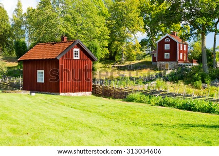 Old red farm buildings in the outskirts of a small village. Vintage fencing surround the different areas and green summer trees grow close to houses. Rural summer landscape in Smaland, Sweden.  - stock photo