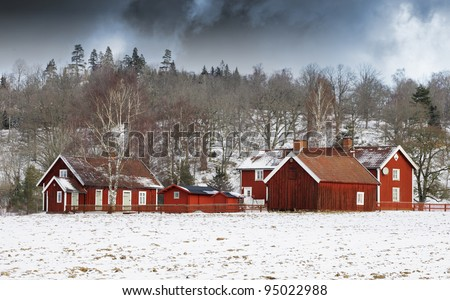 old red farm with dark storm clouds approaching, snow and winter scenery in sweden