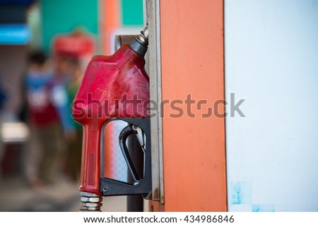 Old red fuel nozzle on gas station for refueling the car - stock photo