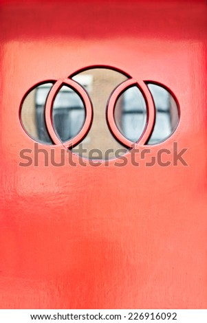Old red home entrance door with round windows  - stock photo