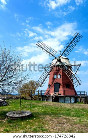 Old red painted windmill of smock mill type with one broken wing on the island of Oeland, Sweden. In the background the Kalmar strait, the strait between Oeland and the Swedish mainland. - stock photo