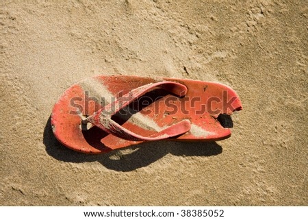 old red plastic sandal abandoned on the beach, top view - stock photo