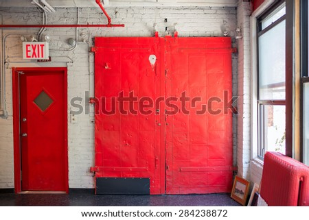 Old red shaft door with exit sign - stock photo