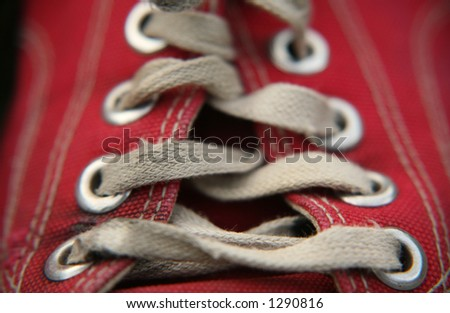 Old red shoe and worn laces with very shallow DoF. - stock photo