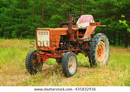Old red tractor on grass