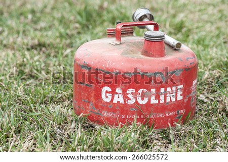 Old red vintage gasoline can background (Shallow DOF) - stock photo