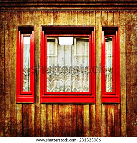 Old red window with curtains of ancient rural wooden house old paper background. Photo in retro style. Paper texture. Aged textured photo in retro style - stock photo