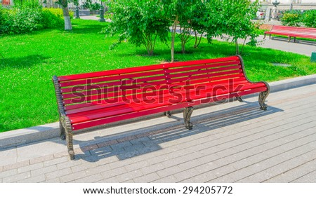 Old red wooden bench in city park