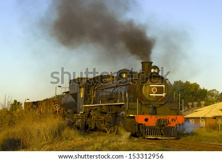 Old reef steamer puffing away through the countryside, with black and white smoke coming out of the funnels. - stock photo