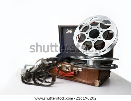 Old reel of film on a brown suitcase - stock photo