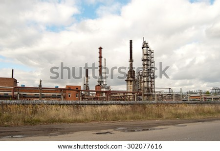 old refinery releasing on the blue sky - stock photo