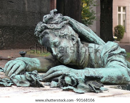 Old, religious art at Cimitero Monumentale. Scene sculptured on a grave depicts a young female lying on a grave mourning after a beloved one. More of this motif in my port. - stock photo