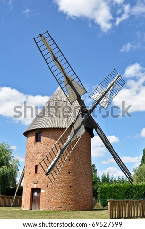 Old renovated windmill with blue sky background - stock photo