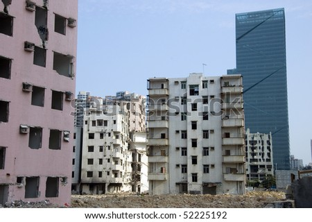 Old residential area ready for demolition and modern skyscraper, Shenzhen city, China. - stock photo