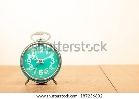 Old retro alarm clock on table - stock photo