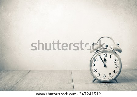 Old retro alarm clock on table. Vintage style sepia photo - stock photo