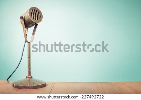 Old retro big microphone front mint green wall background - stock photo