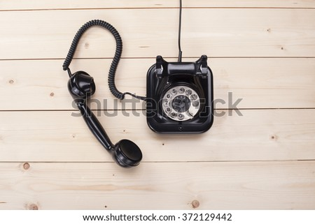 Old retro black phone on wooden board, top view, small DOF, focus on phone - stock photo