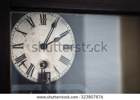 old retro clock with roman numerals behind glass - stock photo