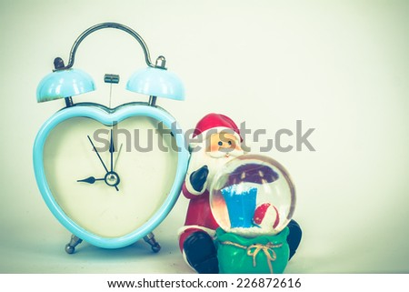 old retro clock with Santa Claus on white background,vintage color tone, abstract background to remind  to time to Christmas holiday. - stock photo