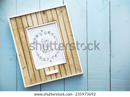 old retro frame over vintage blue wooden  background  ENJOY EVERY MOMENT - stock photo